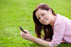 Het jonge zwangere de vrouw van Attrative texting in een park Stock Foto's