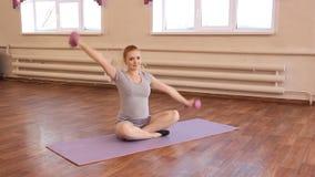 Het jonge zwangere vrouw gymnastiek- doen stock video