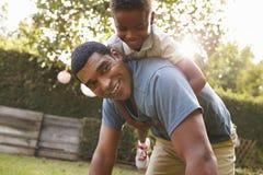 Het jonge zwarte jongen spelen op dadï ¿ ½ s terug in een tuin, lage hoek royalty-vrije stock afbeelding