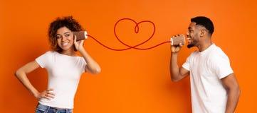 Het jonge zwarte paar met kan op oranje achtergrond telefoneren royalty-vrije stock foto's