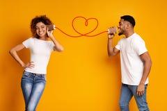 Het jonge zwarte paar met kan op oranje achtergrond telefoneren stock fotografie