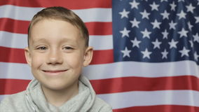 Het jongens` s portret tegen de achtergrond van de Amerikaanse banner Sluit omhoog stock video