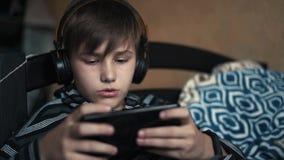 Het jongensblonde luistert muziek in zwarte hoofdtelefoons en speelt een online spel thuis op de zwarte telefoon stock footage