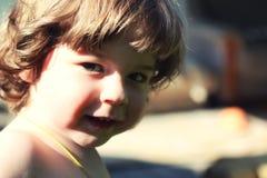 Het jongensjonge geitje zit op moederhanden Stock Fotografie