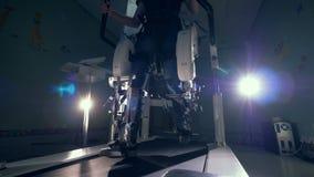 Het jongere versterkt zijn benen op een spoorsimulator Rehabilitatie, rehab, sanering voor mensen met voeten stock video