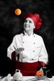 Het jongleren met van de chef-kok met sinaasappel Royalty-vrije Stock Afbeeldingen