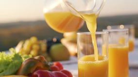 Het jus d'orange wordt gegoten in een glas stock video