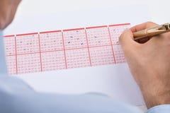 Het Kaartje van Businesspersonmarking on lottery stock fotografie