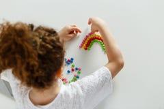 Het kader van beeld van een krullend haired meisje schikte raidbolw van gekleurd suikergoed, op witte tabel, in studio royalty-vrije stock afbeelding
