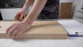 In het kader van de arbeiders` s hand De schrijnwerker merkt de grootte op de houten raad Gebruikt een meetlint en een potlood stock video