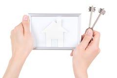 Het kader van de de holdingsfoto van de vrouwenhand met document huis en de sleutels isoleren Stock Afbeeldingen