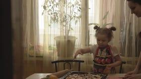 Het kader van de deur, een vrouw met haar dochter die eigengemaakt voedsel voorbereiden stock footage
