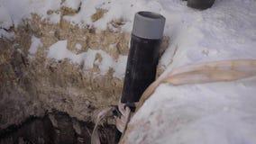 In het kader van een geul in bevroren grond wordt gegraven die De pijp van staal en plastiek wordt gemaakt is in de geul die stock video