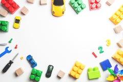 Het kader van het jonge geitjesspeelgoed met bouwblokken, kubussen, stuk speelgoed hulpmiddelen en auto's op witte achtergrond Ho Stock Afbeeldingen