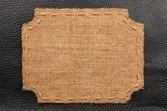 Het kader van jute, ligt op een achtergrond van zwart leer Stock Afbeelding