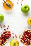 Het kader van Roshhashanah van korrels van granaatappel, honing en appelen op een witte achtergrond Stock Foto's