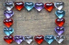 Het kader van Valentine ` s van kleurrijke glasharten wordt gemaakt op oude houten achtergrond die Kader van harten voor Valentij Stock Foto's