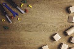 Het kaderachtergrond van het jonge geitjesspeelgoed Kleurrijke stuk speelgoed hulpmiddelen en houten kubussen op bruine houten li Stock Foto's