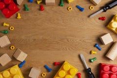 Het kaderachtergrond van het jonge geitjesspeelgoed met stuk speelgoed hulpmiddelen, blokken en kubussen op houten lijst Hoogste  Royalty-vrije Stock Afbeelding