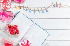 Het kalenderboek op 14 Februari met giftvakje en rood nam boeket toe Stock Foto