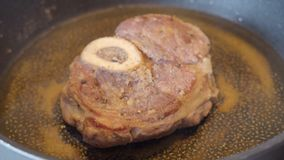 Het kalfsvleeslapje vlees met mergpijp in bloem wordt gepaneerd is gebraden in een pan die
