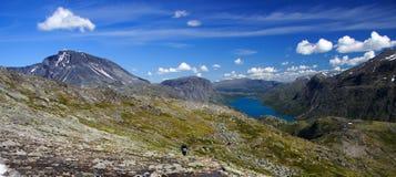 Het kalme landschap van het bergmeer met wandelaar Stock Foto
