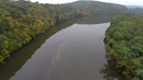 Het kalme luchtschot van de rivierherfst, vlieg boven nog bruin water, stock video