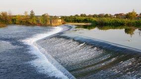 Het kalmeren van rivierwaterval met groene vegetatie op de achtergrond stock afbeeldingen