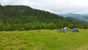 Het kamperen is in bergen Drie tenten op achtergrondbergen Royalty-vrije Stock Foto's