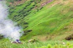 Het kamperen brand en toeristenbowlingspeler met het voorbereiden van voedsel in berg Royalty-vrije Stock Fotografie