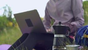 Het kamperen in de bergen Een meisje bereidt koffie op een machine van de geiserkoffie voor Een vrouw werkt ver voor laptop en