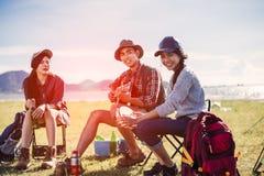 Het kamperen kamp in partij van aard de gelukkige vrienden en het spelen gitaar samen in de zomer stock afbeelding