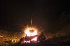 Het kamperen keukengerei - pot op de brand bij een openluchtkampeerterrein bij stock foto's