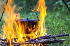 Het kamperen keukengerei - pot op de brand bij een openluchtkampeerterreinverstand Royalty-vrije Stock Foto