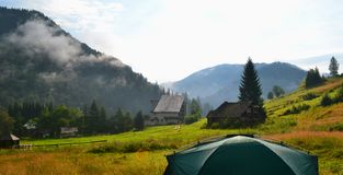 Het kamperen op het gazon dichtbij het huis op binnenplaats Bergdorp onder fogy bergen royalty-vrije stock afbeeldingen