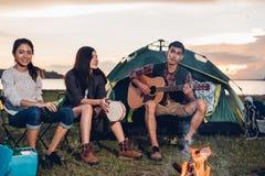 Het kamperen tentkamp in partij van de de groepsnacht van aard de gelukkige vrienden bonf stock afbeeldingen