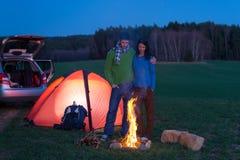 Het kamperen van de tent de tribune van het autopaar door vuur Stock Foto's