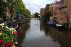 Het kanaal Singel van Amsterdam met typische Nederlandse huizen en woonboten tijdens ochtend blauw uur, Holland, Nederland Het ge Stock Afbeelding
