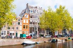 Het kanaal van Amsterdam met auto's en boten langs de bank Stock Fotografie