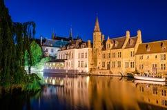 Het kanaal van Brugge bij nacht en middeleeuwse huizen met bezinning in wat Royalty-vrije Stock Fotografie