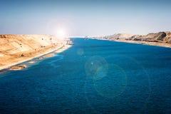 Het Kanaal van Suez - het militaire schip en de sleepboot drijven in 2015 nieuw Stock Afbeelding