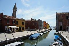 Het kanaal van Venetië met boten en kleurrijke huizen en kerk op Burano-eiland, royalty-vrije stock afbeelding