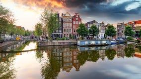 Het Kanaalhuizen van Amsterdam bij zonsondergangbezinningen, Nederland royalty-vrije stock fotografie