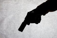 Het kanon in de hand van mensen die klaar om bij zijn slachtoffer is te schieten Het breken van de wet en de misdaad Aanval met e stock fotografie