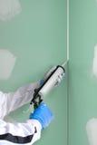 Het kanon van het siliconedichtingsproduct vult de verbinding tussen plasterboars Royalty-vrije Stock Afbeeldingen