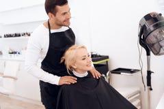 Het kappenkraag van de stilistkleding op rijpe vrouwen` s hals Vrouwelijk kapsel royalty-vrije stock fotografie