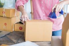Het kartondoos start van de kleine bedrijfseigenaarverpakking op het werk stock afbeelding