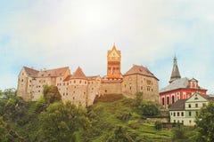 Het kasteel Loket dichtbij stad Karlovy varieert met zon stock foto's