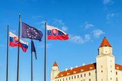 Het kasteel van Bratislava en vlaggen van Slowaakse Europese Unio van de republiek en Royalty-vrije Stock Foto