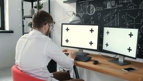 Het Kaukasische arbeider typen op toetsenbord en het bekijken groene het schermjaren '20 4k stock video